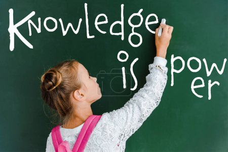 Photo for Schoolchild holding chalk near chalkboard with knowledge is power lettering on green - Royalty Free Image