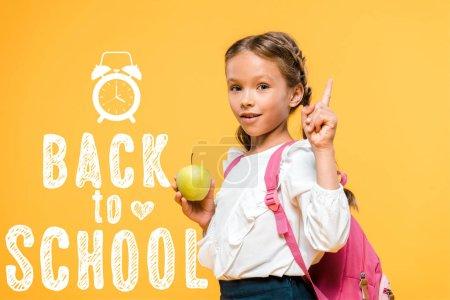 Photo pour Adorable écolier tenant la pomme et pointant avec le doigt près de retour à l'école lettrage sur l'orange - image libre de droit