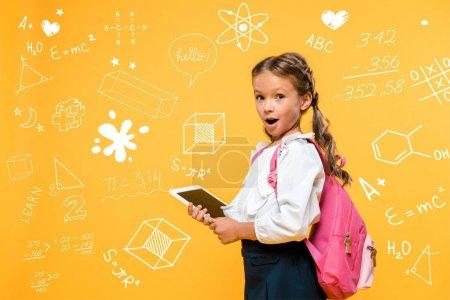 Photo pour Écolier surpris tenant tablette numérique avec écran blanc près de formules mathématiques sur orange - image libre de droit