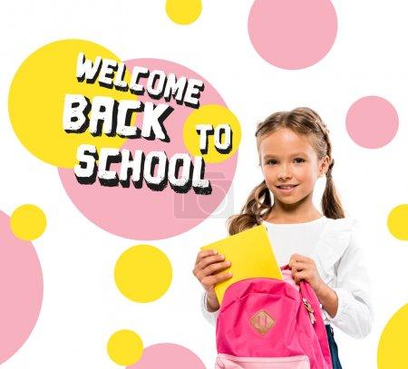 Photo pour Enfant de sourire mettant le livre dans le sac à dos rose près de retour au lettrage d'école sur le blanc - image libre de droit