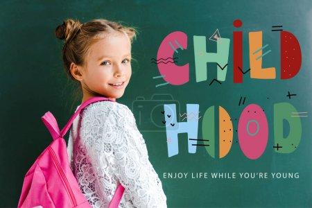 Photo pour Écolier heureux souriant tout en restant avec le sac à dos près du lettrage d'enfance sur le vert - image libre de droit
