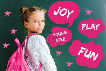 Photo pour Écolier heureux souriant tout en restant avec le sac à dos près de bulle de discours et bulles de pensée avec des mots sur le vert - image libre de droit