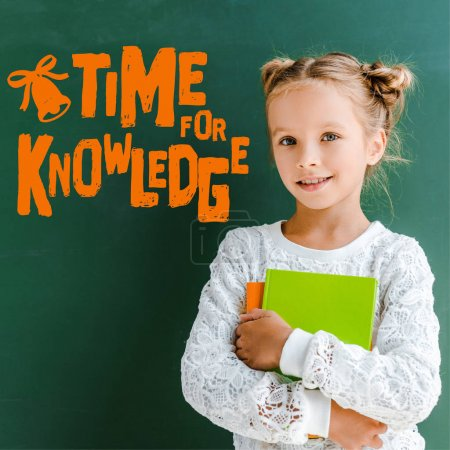 Photo for Happy schoolgirl smiling while standing with books near time for knowledge lettering on green - Royalty Free Image