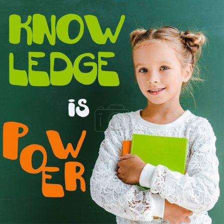 Photo pour Écolière heureuse souriant tout en restant avec des livres près de la connaissance est le lettrage de puissance sur le vert - image libre de droit
