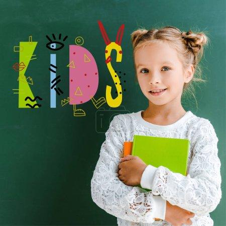 heureuse écolière souriant tout en se tenant avec des livres près des enfants lettrage sur vert
