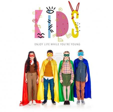 Foto de Niños felices con trajes de superhéroes y máscaras mirando la cámara cerca de los niños letras en blanco - Imagen libre de derechos