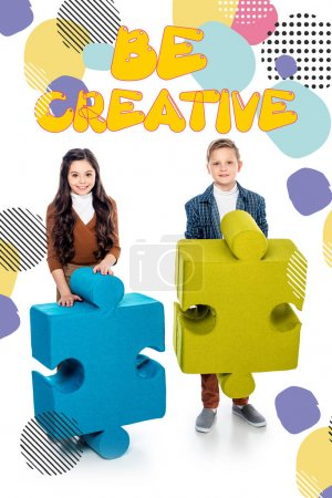 Photo for Happy kids with jigsaw puzzle pieces looking at camera near be creative lettering on white - Royalty Free Image