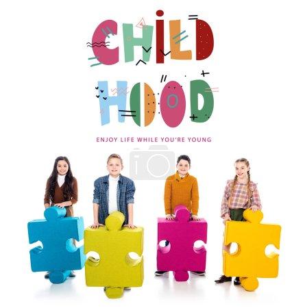 Foto de Niños felices con piezas de rompecabezas mirando la cámara cerca de las letras de la infancia en blanco - Imagen libre de derechos
