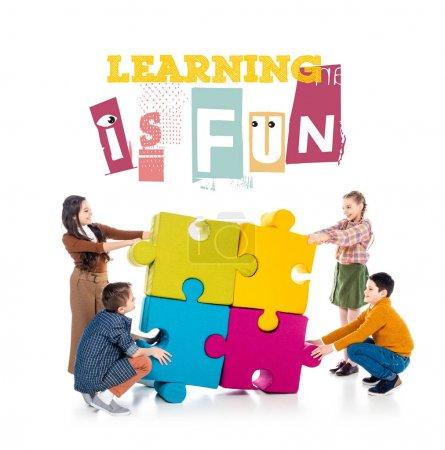 Foto de Niños felices jugando con piezas de rompecabezas cerca del aprendizaje es letras divertidas en blanco - Imagen libre de derechos