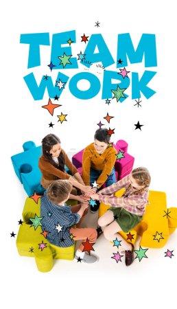 Photo pour Vue d'angle élevé des enfants s'asseyant sur des poufs de puzzle de puzzle et empilant des mains près du lettrage de travail d'équipe sur le blanc - image libre de droit