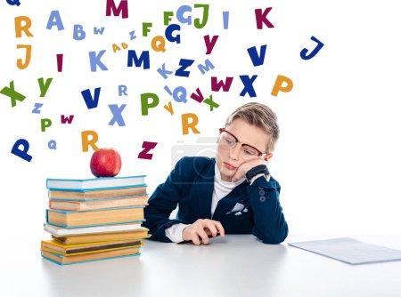 Photo pour Triste écolier dans des lunettes assis au bureau avec des livres et pomme près de lettres colorées sur blanc - image libre de droit