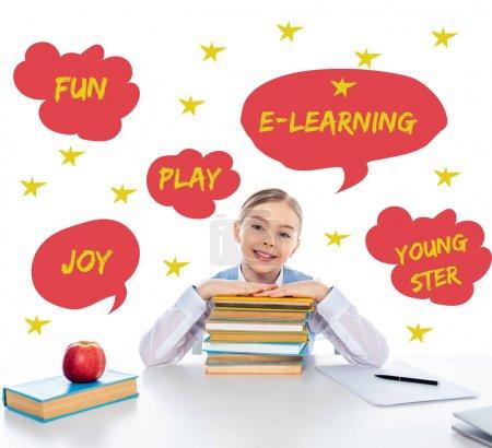 Photo pour Écolière souriante assise au bureau avec des livres et regardant la caméra près des bulles de parole avec des lettres sur blanc - image libre de droit