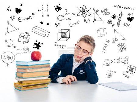 Photo pour Triste écolier dans des lunettes assis au bureau avec des livres et pomme près de formules mathématiques sur blanc - image libre de droit