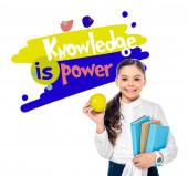 """Постер, картина, фотообои """"улыбающаяся школьница, держащая яблоко и книги, глядя на камеру рядом со знанием, является буквой власти на белом"""""""