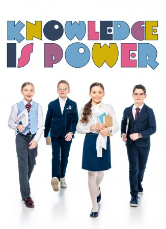 Photo for Schoolchildren pretending to be businesspeople with books and newspaper walking near knowledge is power letters on white - Royalty Free Image