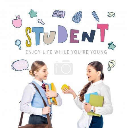 Photo for Schoolgirls in formal wear with books and apple near student letters on white - Royalty Free Image