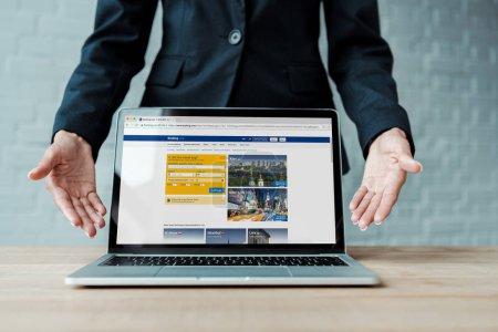 KYIV, UKRAINE - 5 AOÛT 2019 : vue recadrée de la femme gesticulant près d'un ordinateur portable avec site de réservation à l'écran