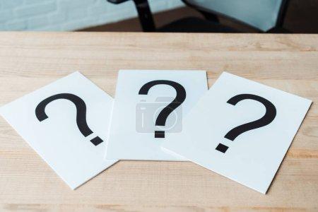 Photo pour Points d'interrogation noirs sur les papiers blancs sur la table en bois - image libre de droit