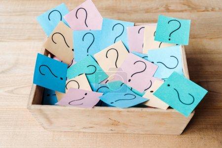 Photo pour Vue au-dessus des notes collantes avec des points d'interrogation dans la boîte en bois sur le bureau - image libre de droit