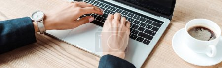 Photo for Panoramic shot of businesswoman typing on laptop near cup with coffee on table - Royalty Free Image