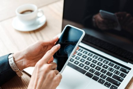 Photo for Cropped view of woman pointing with finger at smartphone with blank screen near laptop - Royalty Free Image