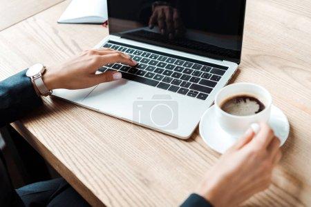 Photo pour Vue recadrée de femme d'affaires tapant sur l'ordinateur portatif avec l'écran blanc près de tasse de café sur la table - image libre de droit