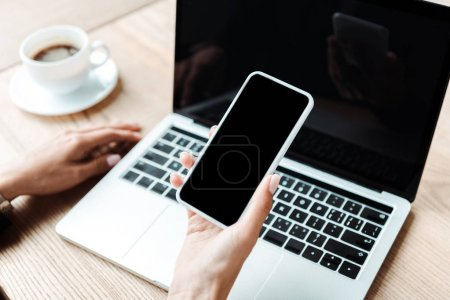 cropped view of woman holding smartphone with blank screen near laptop