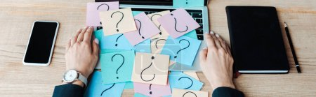 panoramic shot of woman near sticky notes with question marks on laptop