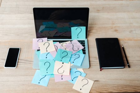 Photo for Overhead view of sticky notes with question marks on laptop near notebook and smartphone - Royalty Free Image