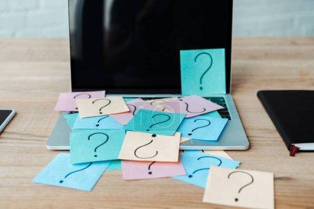 Photo pour Mise au point sélective des notes collantes avec des points d'interrogation sur l'ordinateur portatif avec écran blanc près du cahier - image libre de droit