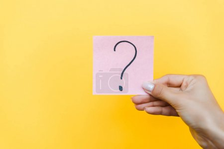 Photo for Cropped view of woman holding sticky note with question mark on orange - Royalty Free Image