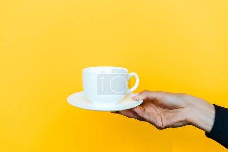 Photo pour Vue recadrée de femme tenant soucoupe et tasse isolée sur orange - image libre de droit