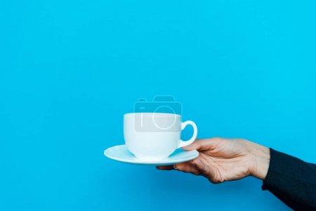 Photo pour Vue recadrée de femme tenant soucoupe et tasse sur bleu - image libre de droit