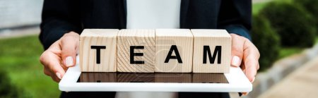Photo for Panoramic shot of woman holding digital tablet and wooden cubes with team letters - Royalty Free Image