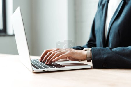 Photo for Cropped view of woman typing on laptop in office - Royalty Free Image