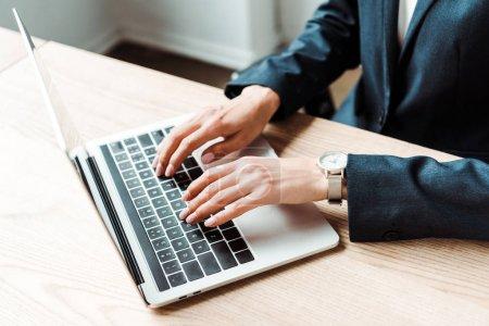 Photo pour Vue recadrée de femme tapant sur l'ordinateur portatif tout en travaillant dans le bureau - image libre de droit