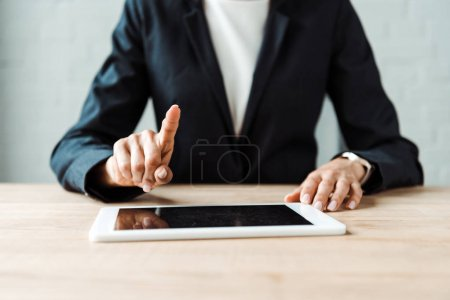 cropped view of woman pointing with finger at digitla tablet with blank screen on table