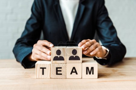 Ausgeschnittene Ansicht einer Geschäftsfrau in der Nähe von Holzwürfeln mit menschlichen Formen und Teambuchstaben