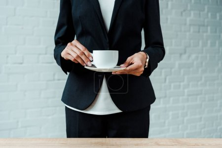 cropped view of woman holding cup with coffee and saucer in office