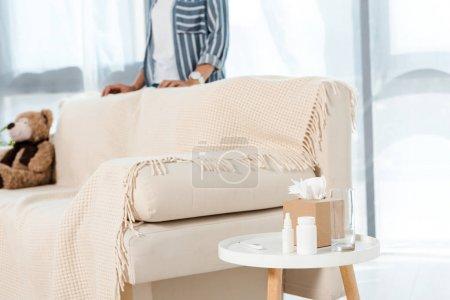 Photo pour Vue recadrée de femme restant près du sofa dans le salon - image libre de droit