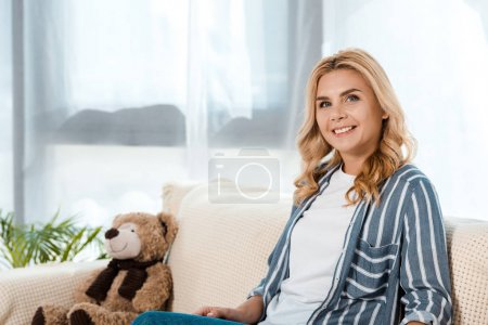 Photo for Happy woman sitting on sofa near soft toy - Royalty Free Image