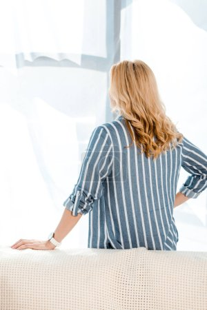 Photo for Back view of blonde woman standing with hand on hip at home - Royalty Free Image