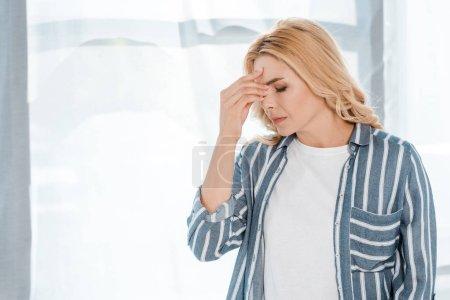 Photo pour Femme émotive touchant la tête tout en ayant le mal de tête à la maison - image libre de droit