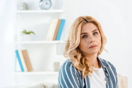 Photo pour Femme triste de mauvaise humeur regardant la caméra dans le salon - image libre de droit
