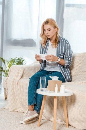 Photo pour Femme malade s'asseyant sur le sofa et retenant la serviette près du verre avec l'eau - image libre de droit