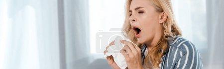 Panoramaaufnahme einer Frau mit Serviette und Niesen zu Hause