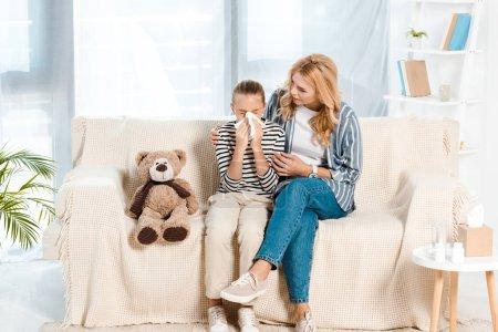 Photo pour Mère s'asseyant avec le descendant malade éternuant dans le tissu - image libre de droit