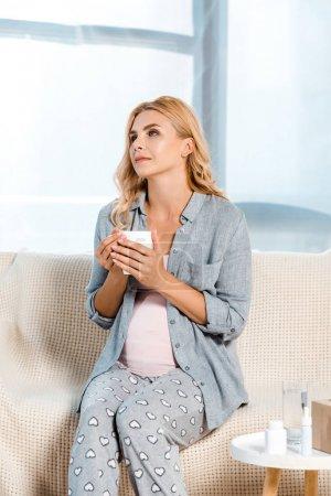 Photo pour Femme enceinte s'asseyant sur le sofa et retenant la tasse à la maison - image libre de droit