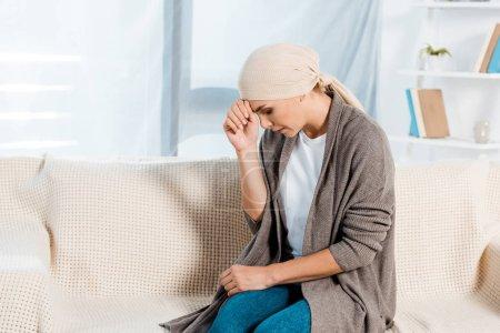 Photo pour Femme bouleversée et malade avec l'écharpe de tête dans le salon - image libre de droit