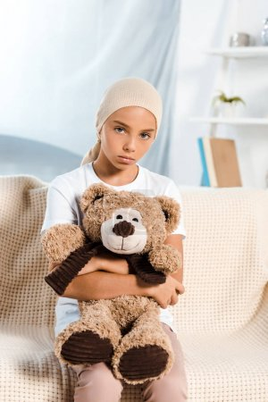 Photo for Sick kid sitting on sofa and holding teddy bear - Royalty Free Image